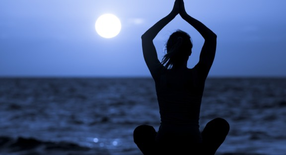 Silhouette of woman in lotus position sitting on the beach and medditating with her hands raised